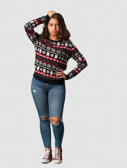 Full body young woman wearing a christmas jersey worried and overwhelmed