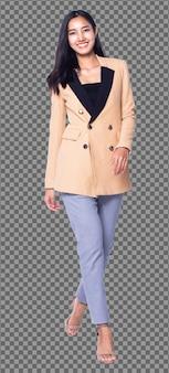 Фигурка в полный рост, азиатская бизнес-леди 20-х годов, умная в кремовых брюках костюма-блейзера, изолирована. загорелая кожа девушки с длинными прямыми черными волосами идет навстречу улыбке на белом фоне.