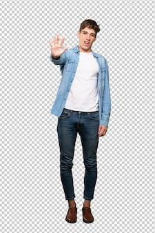 A full length shot of a handsome young man counting five with fingers