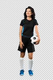 A full length shot of a young football player woman looking up while smiling