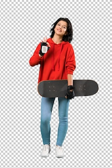 A full length shot of a young skater woman showing ok sign with fingers