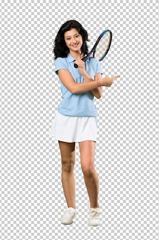 A full length shot of a young tennis player woman pointing to the side to present a product