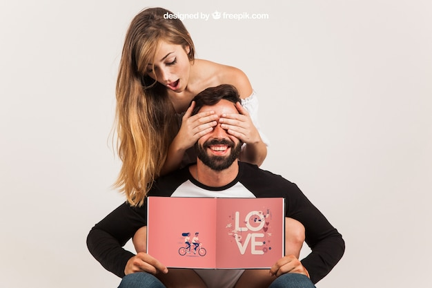 Funny couple holding open book