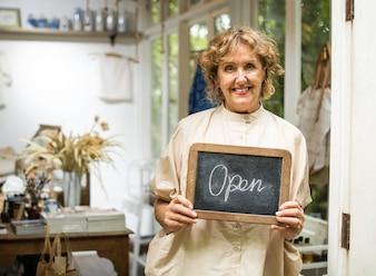 Garden shop owner holding an open sign