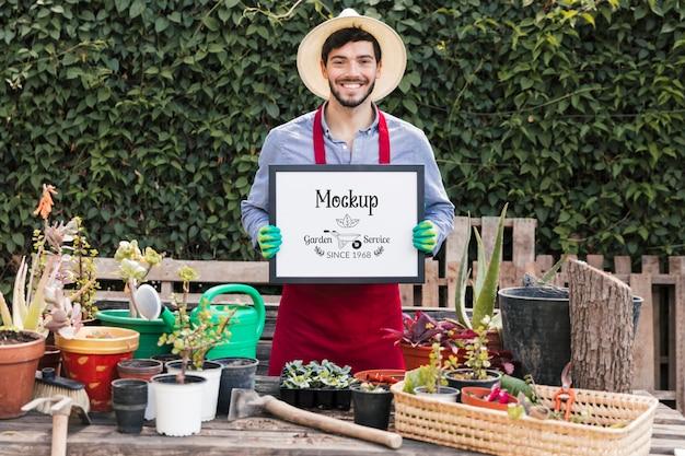 Садовник держит макет знак