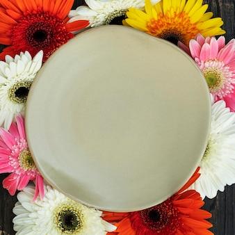 Цветы герберы, окружающие тарелку
