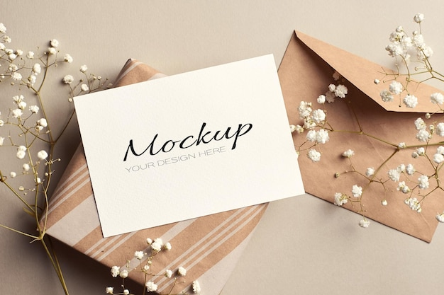Ggreeting card or invitation mockup with envelope, gift box and white hypsophila flowers