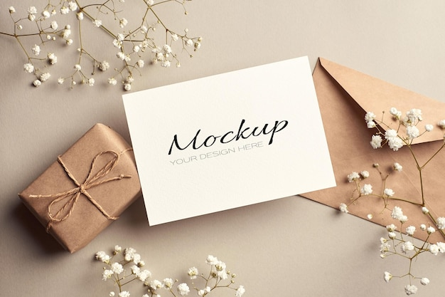 Ggreeting card stationary mockup with envelope, gift box and white hypsophila flowers