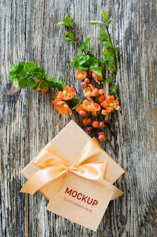 Gift box with bow ribbon, blank tag and delicate flowering branch.