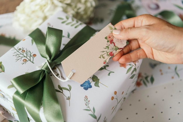 Gift box wrapped with floral patterned paper with a card mockup