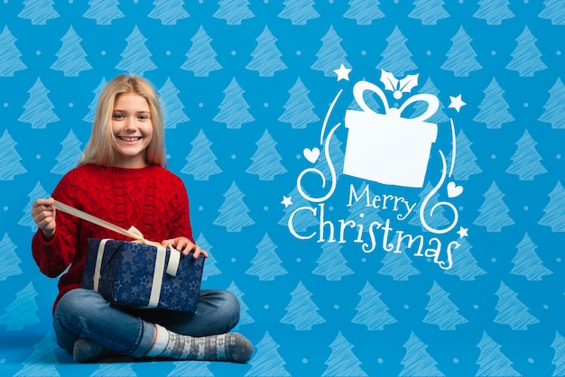 Girl dressed in christmas thematic sweater opening gift