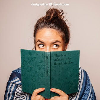 Girl hiding face behind book