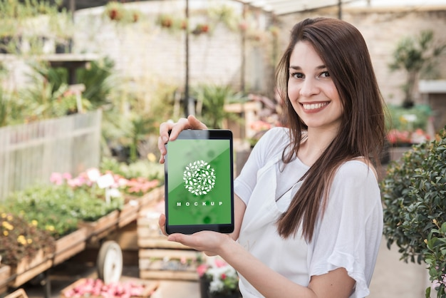 Girl holding tablet mockup with gardening concept