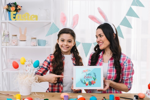 Girl and mother with tablet mockup on easter day