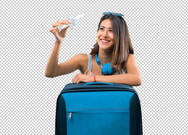 Девушка путешествует с чемоданом и держит игрушечный самолетик