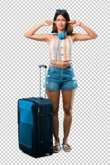 Girl traveling with her suitcase covering both ears with hands. frustrated expression