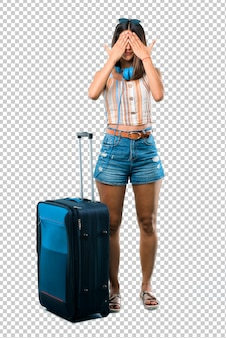 Girl traveling with her suitcase covering eyes by hands. do not want to see something