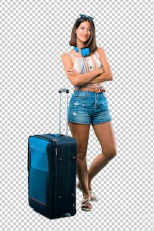 Девушка путешествует с чемоданом, держа руки скрещенными в переднем положении. уверенное выражение