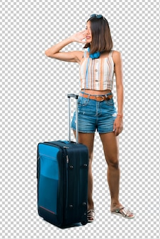 Girl traveling with her suitcase listening something