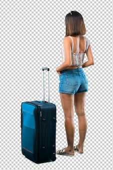 Girl traveling with her suitcase looking back