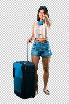 Girl traveling with her suitcase points finger at you with a confident expression