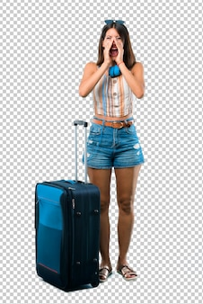 Girl traveling with her suitcase shouting with mouth wide open to the lateral