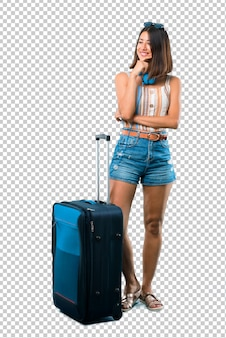Girl traveling with her suitcase smiling a lot while putting hands on chest