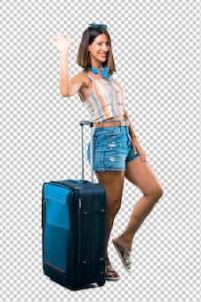 Girl traveling with her suitcase smiling and saluting