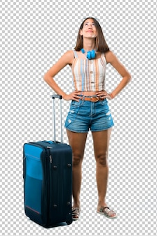 Girl traveling with her suitcase stand and looking up