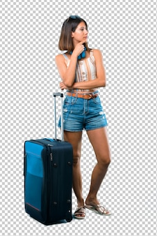 Girl traveling with her suitcase standing and looking to the side