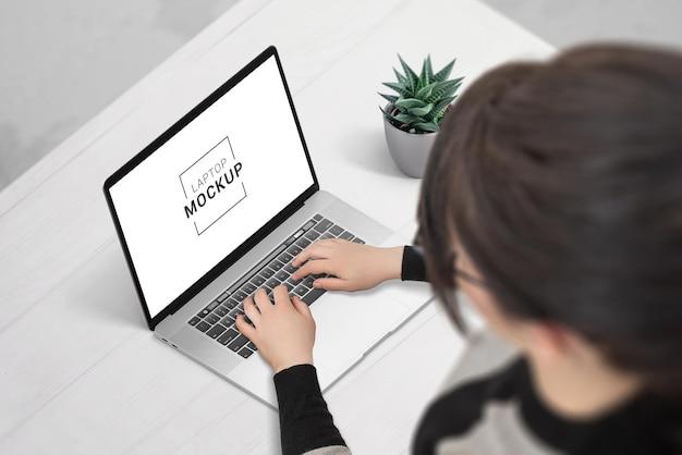 Девушка печатает на офисном столе макета ноутбука