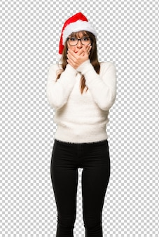 Girl with celebrating the christmas holidays covering mouth for saying something inappropr