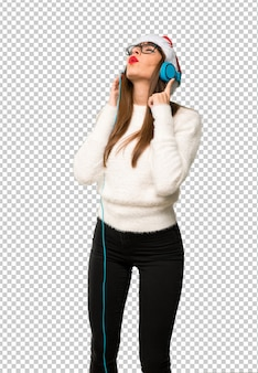 Girl with celebrating the christmas holidays listening to music with headphones