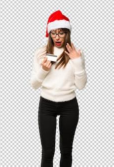 Девушка с празднованием рождественских праздников с кредитной картой и удивлен