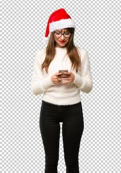 Девушка с празднованием рождественских праздников отправляет сообщение или электронную почту с мобильного