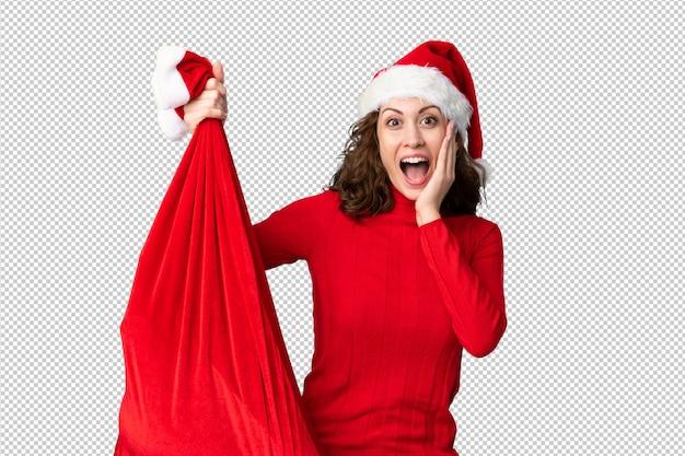 Девушка с шляпой рождества держа сумку рождества полную подарков