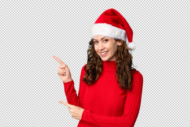 Girl with christmas hat pointing finger to the side