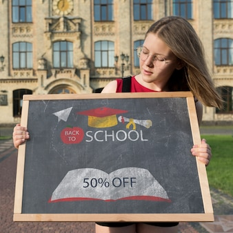 Girl with glasses holding a blackboard mock-up
