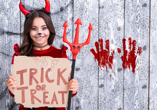 Girl with trick or treat sign holding the devil trident