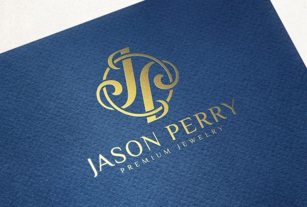 Макет логотипа с тиснением золотой фольгой на темно-синей фактурной бумаге