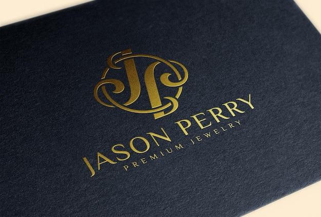 Тиснение золотой фольгой логотипа на черной бумажной визитной карточке