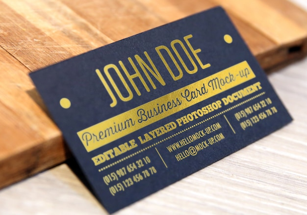 Gold letterpress on black paper business card mockup with gold letters on wooded background