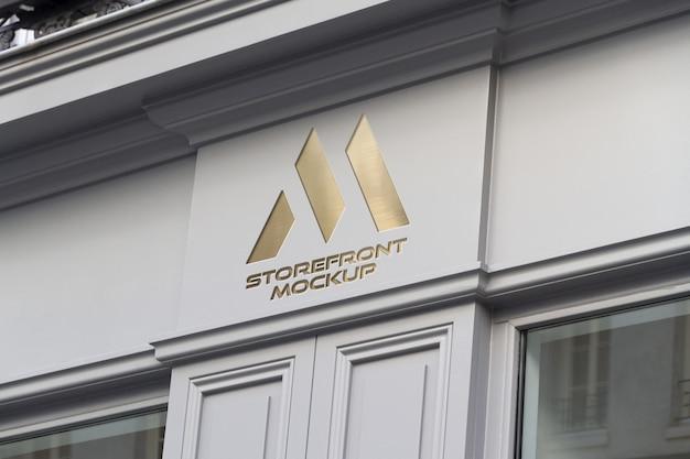 Золотой логотип на витрине в уличном макете