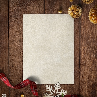 Gold paper mockup with christmas decorations on wooden background