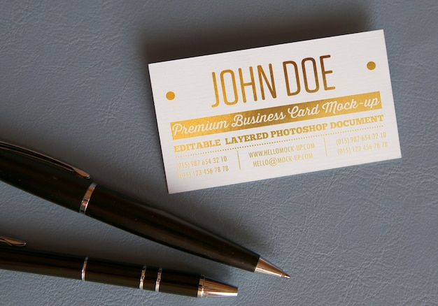 Gold pressed letters business card mockup template on leather surface with two premium pens
