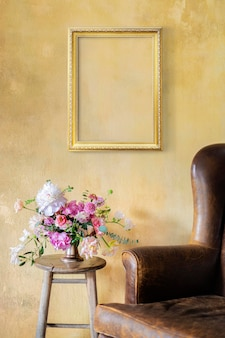 Golden frame on a yellow wall by flowers