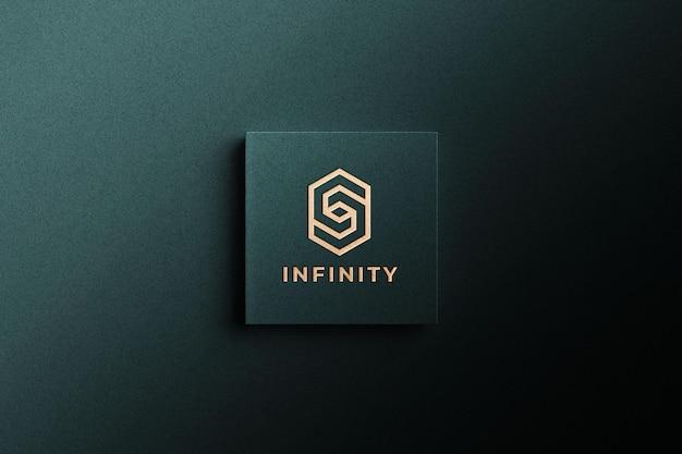 Макет золотого логотипа на зеленой бумаге
