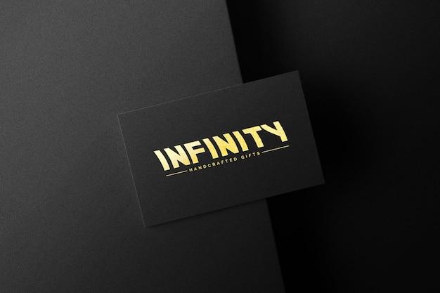 Золотой логотип на черной бумаге макет