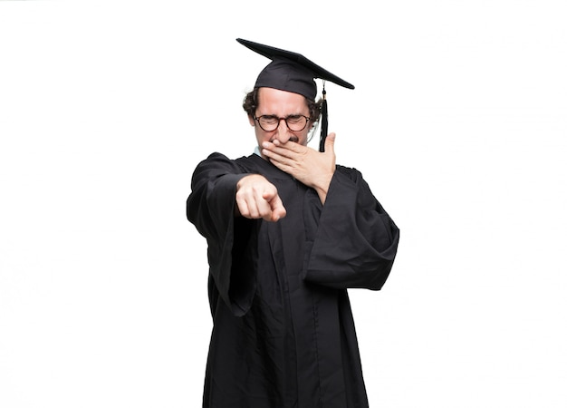Graduate bearded man laughing hard at something hilarious and pointing sideways while covering mouth
