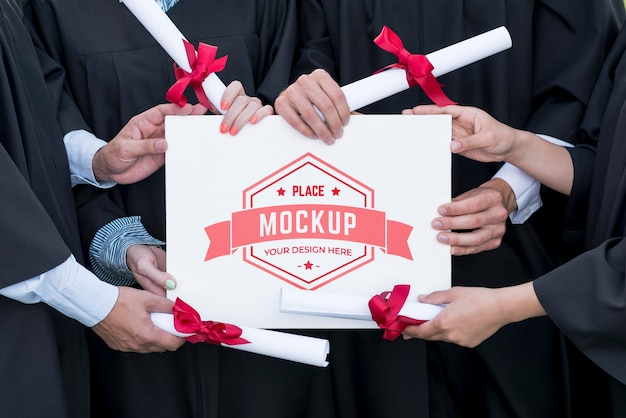 Graduates holding a mock-up diploma